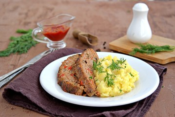 A meatloaf with mushrooms and red sweet pepper on a white plate with a garnish of mashed potatoes. Selective focus.