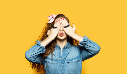 Portrait of lovely model sending air kiss with fake eyelashes on hands. Long-haired woman in jean jacket posing for picture on yellow background. Emotions and fun concept