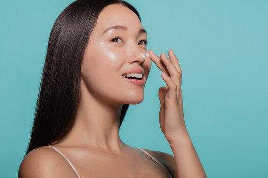 Dazzling woman applying moisturizing cream