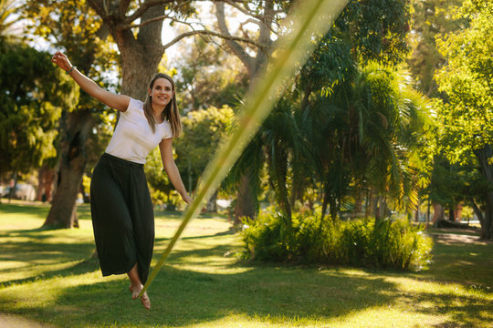 Woman walking on rope in a park