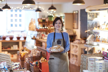Portrait Of Smiling Female Owner Of Delicatessen Shop Wearing Apron Holding Loaf Of Bread