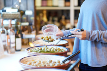 Close Up Of Female Customer In Delicatessen Filling Pot With Green Olives