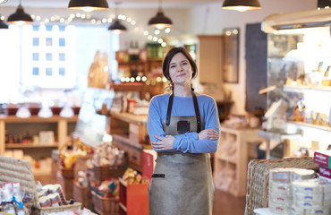 Portrait Of Smiling Female Owner Of Delicatessen Shop Wearing Apron