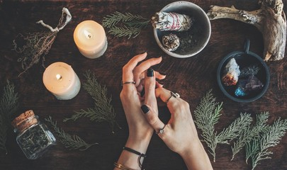 Witches hands on a table ready for spell work. Wiccan witch altar filled with sage evergreen branches herbs crystals and burning white candles. Wearing vintage jewelry on her hands