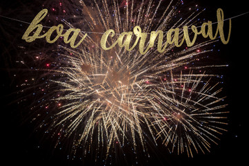 Boa Carnaval, Portuguese for Happy Carnival message in elegant shiny gold script strung in front of bursts of golden fireworks in Rio de Janeiro, Brazil