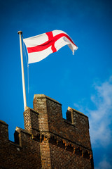England flag fluttering above English castle in Surrey