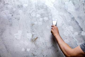 Löcher und Risse in einer Wand werden mit Füllmaterial oder Gips zugespachtelt