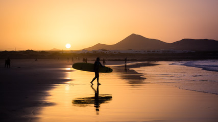 Silhouette of a Surfer on Famara beach at sunset