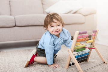 Adorable baby boy playing with colorful scores at home