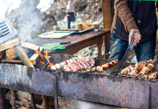 Man cooks shish kebab on the grill in the open air