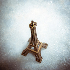 Souvenir model of the Eiffel Tower on cement floor. Strong vignette, split toning effect and film grain filters.