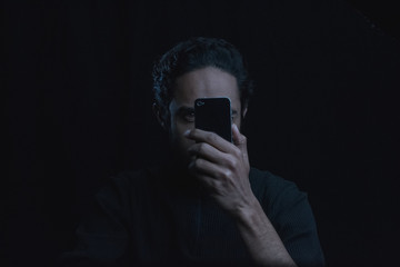 auto portrait of man in the shadows with low key cell