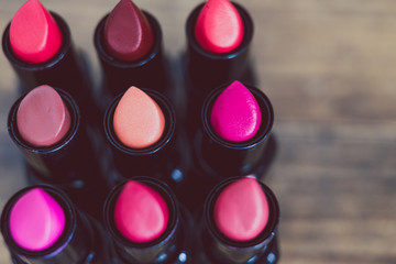 group of red pink and nude lipsticks lined up on wooden table
