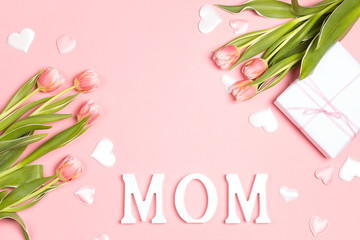 Mothers day message with tulips and gift on pink background. Copy space, flat lay, top view.