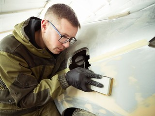 Cute guy in black glasses with black gloves displays the shape of the hood for the subsequent painting of the car. guy - a house painter working on a car in the garage
