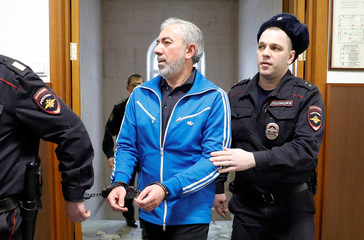 Partner in the Baring Vostok private equity group Abgaryan is escorted inside a court building in Moscow