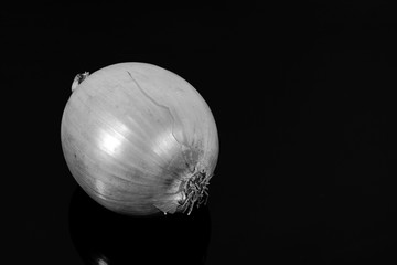 onions reflected on a black mirror table