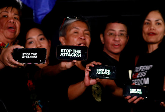 """Journalists, including Rappler CEO Maria Ressa, raise their smart phones with words """"STOP THE ATTACKS!"""" in a rally for press freedom in Quezon City"""