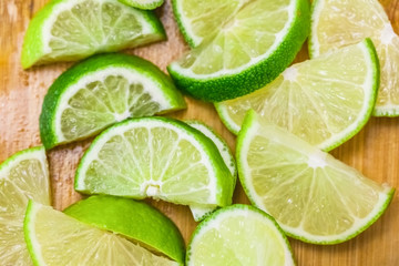 lime slices on wooden table, close up blurry background