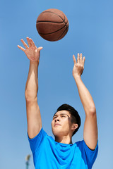 young asian man shooting basketball