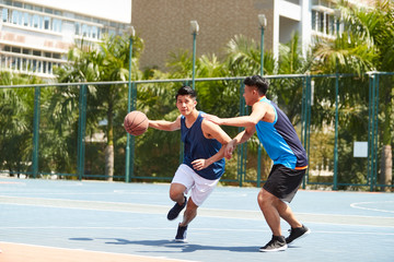 two young asian men playing basketball on outdoor court