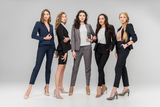 beautiful successful women standing with hands in pockets on grey background