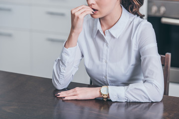 cropped view of sad woman in white blouse sitting by table in kitchen, grieving disorder concept