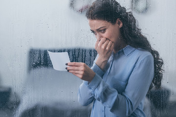 grieving woman holding photograph, covering mouth with hand and crying at home through window with raindrops
