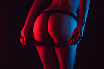 Sexy erotic ass of a girl in a Thong with a whip for BDSM
