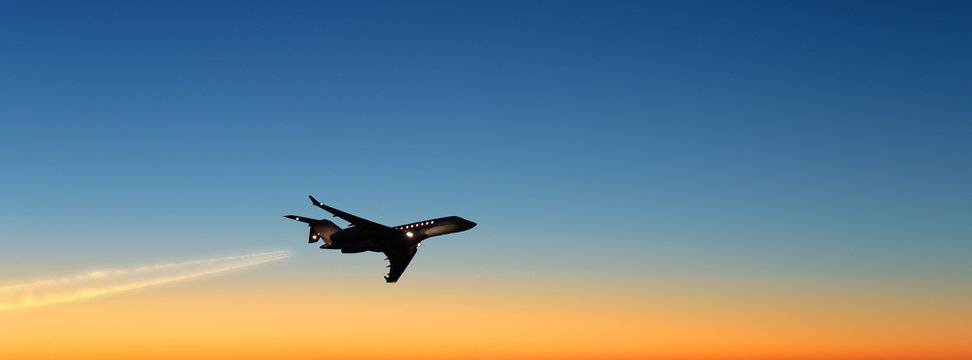 business jet airplane flying on beautiful sunset sky landscape background at dusk dawn time scenic aerial up silhouette plane view corporate air travel concept wide panorama banner