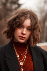 Fashion portrait of young curly girl with blue eyes, red lips and freckles