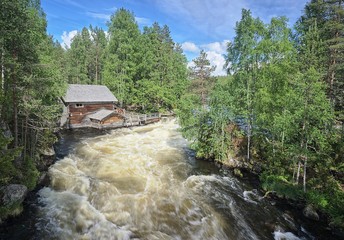 Old watermill along the fast-moving Myllykoski rapids at the Oulanka National Park in Kuusamo, Finland. The view is from a hanging bridge over the river. Beautiful, sunny summer day for hiking.