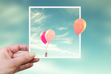 Hand holding an instant photo with air balloons, think outside the box concept