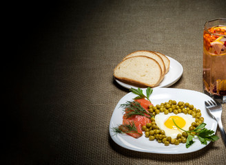 Fried eggs with peas and red fish on a white plate. Berry juice and white bread on the table. Place for inscription.
