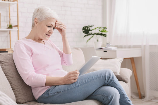 Confused senior woman using tablet computer at home