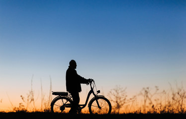 Active pension. Male cyclist on the e-bike or electric bicycle on the sunset background. Silhouette of the old man in profile. Travel. Sport.