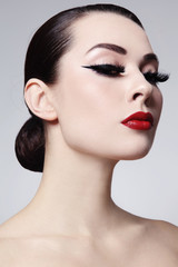 Portrait of young beautiful woman with red lips and cat eye make-up