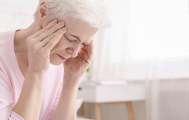 Senior woman having headache and touching her temples Wall mural