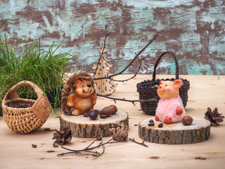 A fabulous picture with small toys, a Hedgehog and a pink pig are resting on stumps, tired of harvesting nuts in the forest