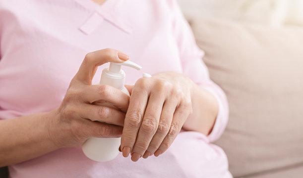 Hands senior woman with moisturizing cream closeup