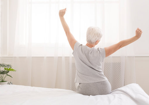 Senior woman sitting on her bed in morning