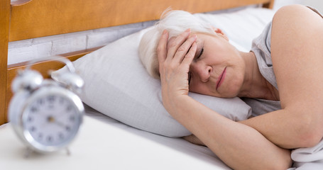 SEnior woman suffering from insomnia in bed Wall mural