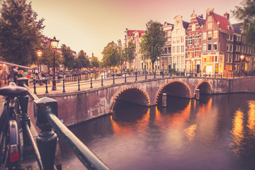 Wall Mural - View of the City of Amsterdam with canal and bridge seen at sunset with vintage filter