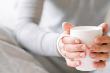 Morning coziness. Man in pyjamas holding white cup of favorite drink.