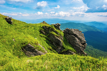 rocky cliff on a grassy slope. beautiful scenery in mountains. huge ridge in the distance. wonderful summer weather