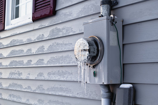 Frozen electrical utility meter on house  exterior siding.