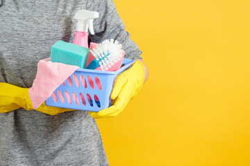 Home cleaning concept. Plastic basket with supplies in hands. Copy space on yellow background.