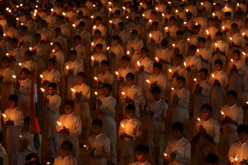Students hold candles during a vigil to pay tribute to CRPF personnel who were killed after a suicide bomber rammed a car into a bus carrying them in south Kashmir on Thursday, inside a temple in Ahmedabad