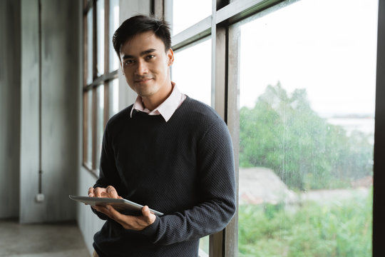 handsome asian young businessman using tablet pc