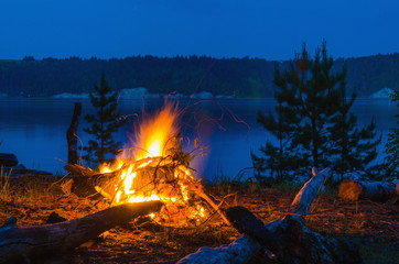 Big night bonfire at the shore of the river in a forest glade, flames, sparks.
